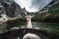 Huwelijkspaar het kussen dichtbij het meer in Tatra-bergen in Polen Morskie Oko De mooie Dag van de Zomer stock afbeelding