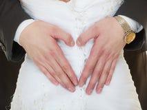 Huwelijkspaar. Mannelijke handen die hart maken liefde gestalte geven Stock Foto