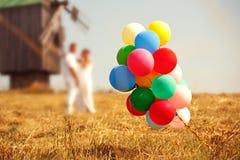 Huwelijkspaar met kleurenballons Stock Foto's