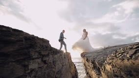 Huwelijkspaar samen op de helling van de berg dichtbij overzees Mooie bruidegom en bruid Langzame Motie stock video