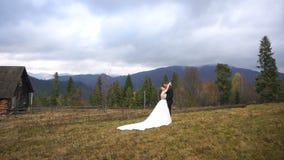 Huwelijksportret van de jonggehuwden die teder in het de herfstdorp koesteren in de bergen De knappe bruidegom kust stock video
