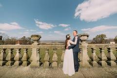 Huwelijksportret van gelukkig het omhelzen van het modieuze van de jonggehuwdebruid en bruidegom stellen bij oud steenterras in d stock foto's