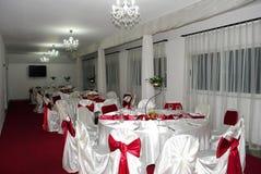 Huwelijksregeling met mooie kroonluchter en witte en rode stoelen royalty-vrije stock foto