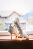 Huwelijksschoenen en parelhalsband Stock Foto's