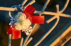 Huwelijksslot met witte rozen en rood lint op de metaalbrug stock afbeelding