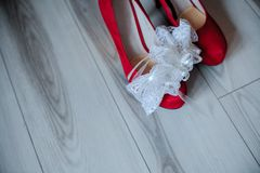 Huwelijkstoebehoren in de vorm van rode schoenenbruid en kouseband Stock Afbeelding