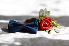Huwelijkstoebehoren van de bruidegom, donkerblauwe vlinder met een bloemboeket stock fotografie