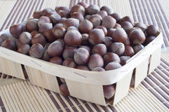 Huzelnuts in a wicker basket. Huzelnuts in a wicker basket on a table covered with a thatched napkins Royalty Free Stock Photos