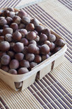 Huzelnuts in a wicker basket on a table. Huzelnuts in a wicker basket on a table covered with a thatched napkins. Vertical. Close-up Royalty Free Stock Photo