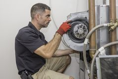 HVAC repair man working on a heat pump. HVAC technician removing a furnace blower motor from a commercial heat pump. Repair man wearing a uniform and safety stock images
