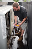 HVAC Technician Working. A young HVAC technician working on a commercial air system on the rooftop Royalty Free Stock Images