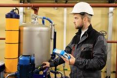 HVAC utrzymania inżynier sprawdza technicznych dane ogrzewania wyposażenie w kotłowym pokoju obrazy stock