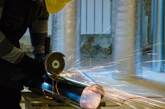 HVAC worker cutting metallic ductwork with the modern angle grinder. HVAC worker cutting metallic ductwork with the angle grinder royalty free stock images