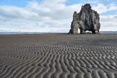 Hvitserkur basalt formation. Stone formation on the dark volcanic sand on the background of the blue sky with clouds. It is Hvitserkur during low tide in Iceland Stock Photos