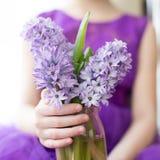 Hyacinter i en vas i händerna av en flicka royaltyfri bild