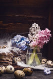 Hyacinths flowers bunch and quail eggs with feathers on rustic wooden background, side view royalty free stock photos