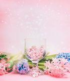 Hyacinths flowers and glass hearts in wineglass over light pink background. Royalty Free Stock Images
