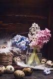 Hyazinthen blüht Bündel- und Wachteleier mit Federn auf rustikalem hölzernem Hintergrund, Seitenansicht lizenzfreie stockfotos