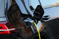 Hybrid car charging power on the street Royalty Free Stock Images