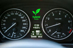 Hybrid car dashboard. Close up of car dashboard with green hybrid mode icon on Royalty Free Stock Photography