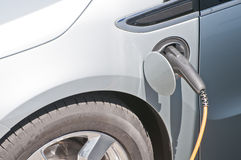 Hybrid electronic car connected to electronic powe. R charger recharging the battery Royalty Free Stock Images