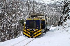 Hybrid locomotive in snow. Passenger train, mountain rail. Hunga. Rian forest railway at winter. 02-18-2018 Royalty Free Stock Photos