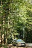 Hybrid- Volvo S60 utövande bil som parkeras i mitt av gräsplan för Arkivbilder