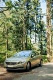 Hybrid- Volvo S60 utövande bil som parkeras i mitt av gräsplan för Royaltyfri Fotografi