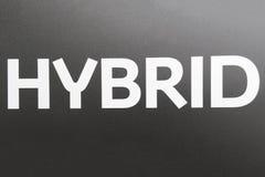HYBRIDE inschrijving op een grijze achtergrond stock fotografie