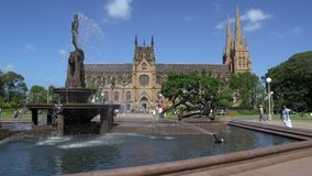 Hyde park fountain with St Mary Cathedral on the background in sydney stock footage
