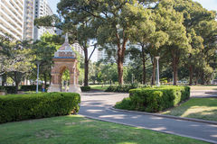 Hyde Park Pergola. SYDNEY,NSW,AUSTRALIA-NOVEMBER 18,2016: Tourists walking through the lush greenery at Hyde Park with pergola and city buildings in downtown Royalty Free Stock Photography