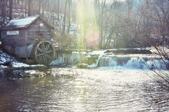 Hyde`s Mill - Ridgeville, Wisconsin. The historic landmark, Hyde`s Mill in the winter with water flowing over the dam and sunlight rays shining on the water royalty free stock image