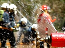 Hydrant. In foreground with fire fighters at work Royalty Free Stock Photo