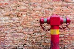 Hydrant an der schmutzigen Backsteinmauer Lizenzfreies Stockbild