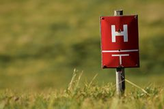 Hydrant on the lawn. A red table with a white H placed on the lawn indicates a hydrant. The hydrant serves to connect a fire hose to a water pipe and thus Royalty Free Stock Photos