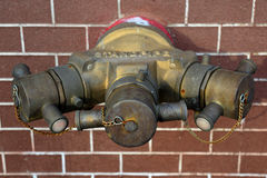 Hydrant with water hoses and fire extinguish equipment on brick Royalty Free Stock Image