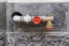 Hydrant with water hoses and fire extinguish equipment on wall.  Stock Photos