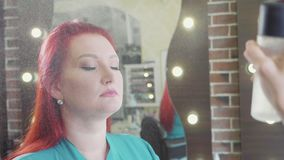 Hydratant le jet arrose sur le visage de la femme après procédure de maquillage banque de vidéos
