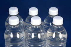 Hydrate Yourself!. Six water bottles on a blue background Stock Photos