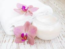 Hydrater crème avec les orchidées roses images stock