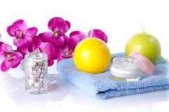 Hydrater la crème avec des bougies et la fleur sur une serviette Photo stock