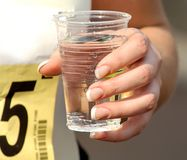 Hydrating. A closeup of a cup of water, held in the hands of an athlete, probably a marathon runner Royalty Free Stock Photos