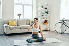 Hydrating. Beautiful young woman in sports clothing practicing yoga and drinking yoga while spending time at home royalty free stock photography