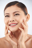 Hydrating lotion. Beautiful woman using hydrating lotion for her skin Royalty Free Stock Image