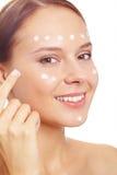 Hydrating skin. Fresh woman applying hydrating cream onto her face Royalty Free Stock Photos