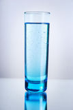 Hydration. Glass of liquid on a reflective surface. Blue tint royalty free stock photo