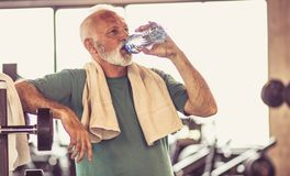 Hydration after exercise is important. Senior man taking break after hard exercise and sitting on floor stock images