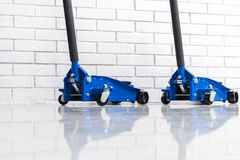 Hydraulic car floor jacks. Car Lift. Blue Hydraulic Floor Jack For car Repairing. Extra safety measures.  stock photos