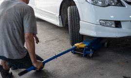 Hydraulic car jack to lift car for check the wheel.  stock image
