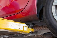 Hydraulic car lift arm holding a vehicle. Hydraulic car lift arm holding a red vehicle in a workshop extreme closeup royalty free stock image